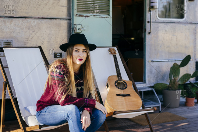 Beautiful young lady in stylish outfit sitting on chair near aged van and playing acoustic guitar
