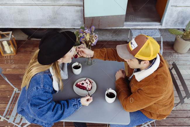 Young man and woman enjoying delicious cake while sitting at table near grungy van