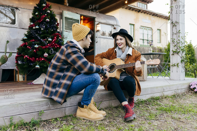 Attractive young female playing acoustic guitar for smiling boyfriend while sitting on terrace near Christmas tree and camper