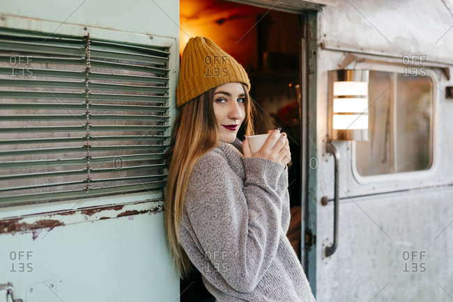 Charming young female in trendy outfit smiling with a mug while standing in entrance of shabby camper