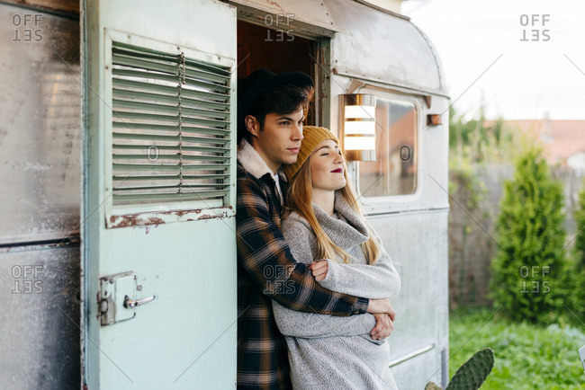 Handsome young guy hugging beautiful girlfriend from back while standing in doorway of retro van in countryside