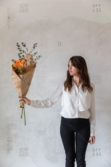 Lovely female in elegant outfit holding pretty flowers wrapped in paper while standing near shabby cement wall