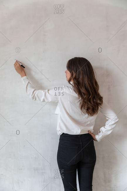 Back view of adult female in elegant outfit keeping hand on waist and writing on clean concrete wall with marker pen