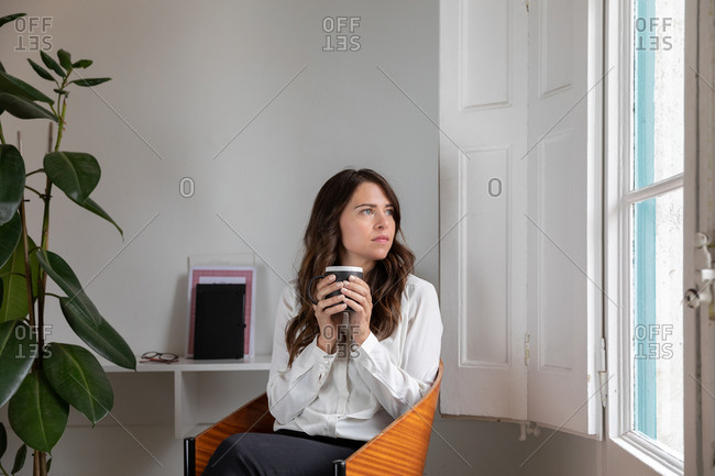 Attractive female in elegant outfit holding cup of fresh hot drink and looking out window while sitting on comfortable chair in cozy room