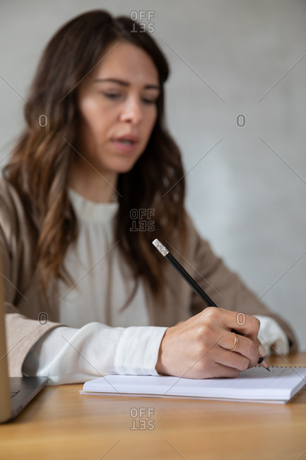 Young woman writing her ideas in a notebook