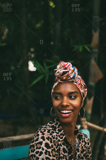 Woman with head wrap sitting in a beautiful garden