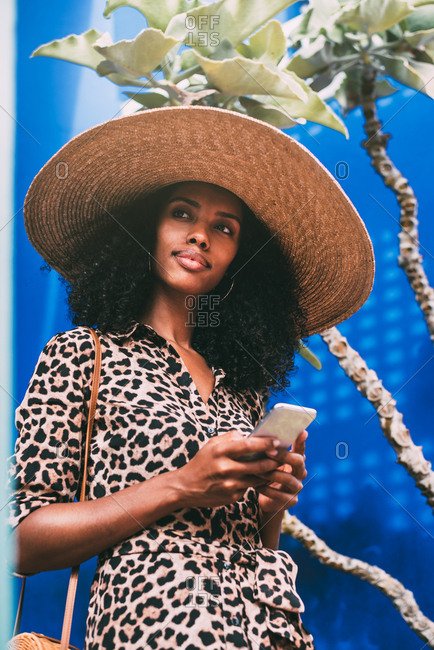 Woman with a straw hat walking in a beautiful architecture talking on the mobile phone