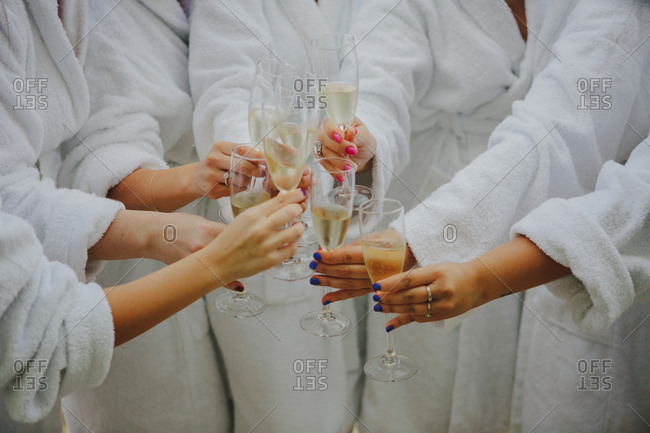 Unrecognizable young women in white bathrobes clinking goblets with fine champagne