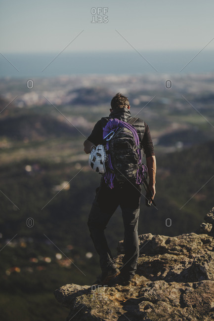 Back view of man with backpack and climbing equipment standing on top of Garbi Mountain and looking at majestic nature on sunny day in Djibouti