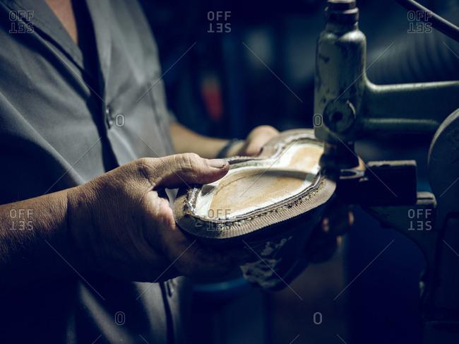 Unrecognizable craftsman making shoes on machine