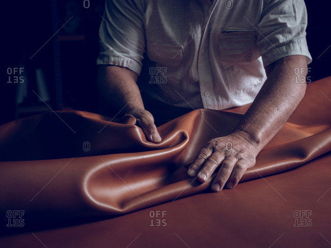 Crop craftsman laying leather on table