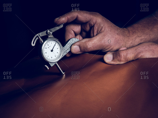 Hands of anonymous craftsman using old gauge to measure thickness on brown leather in dark workshop