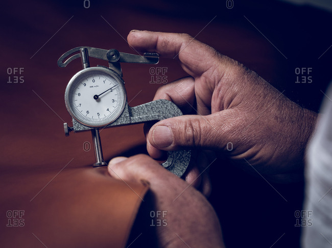 Crop hands measuring thickness of leather
