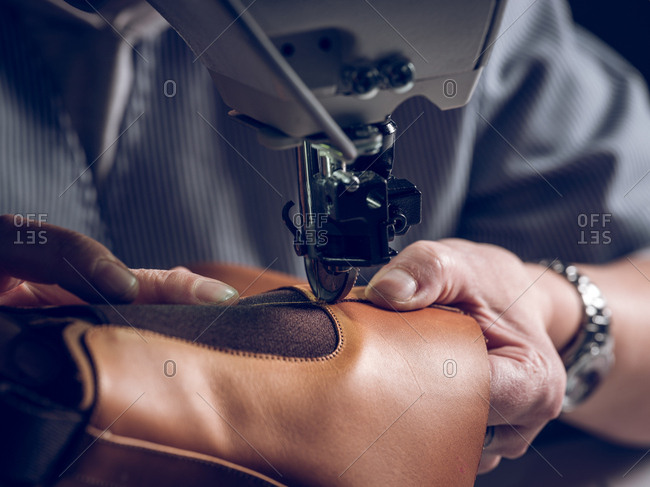 Unrecognizable man using professional machine to sew piece of brown leather for shoe