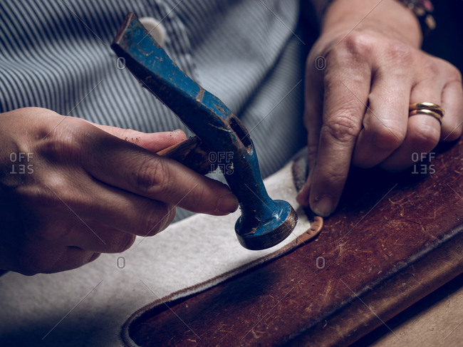 Closeup anonymous man using hammer while working with piece of leather in workshop