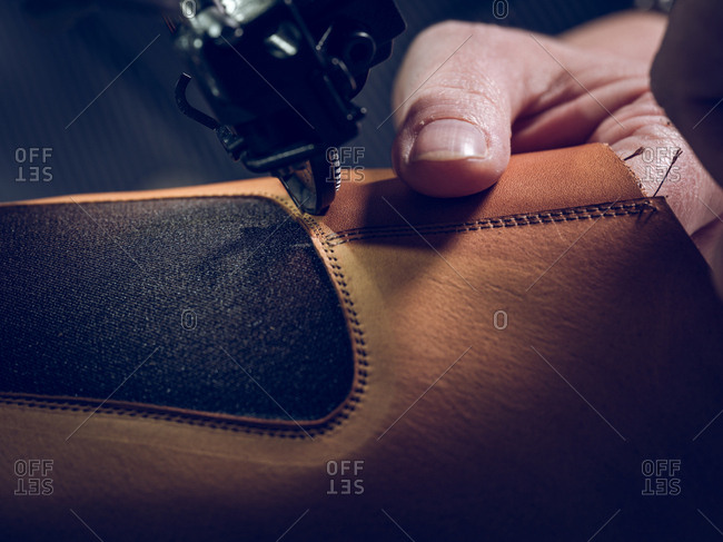 Crop craftsman sewing piece of leather