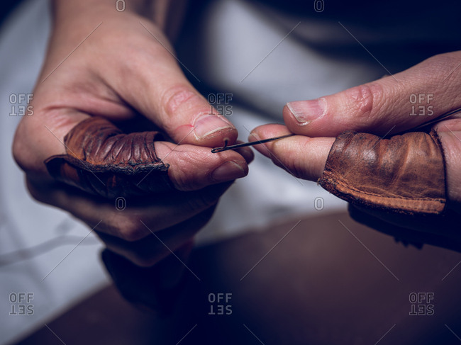 Closeup hands of unrecognizable craftsman putting thread into needle while working in workshop