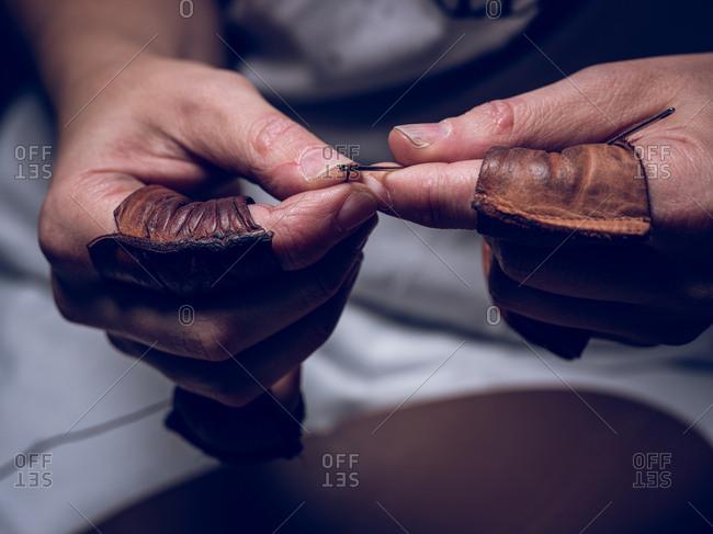 Crop hands preparing needle and thread