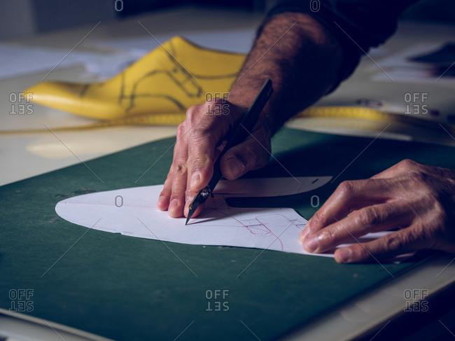 Crop hands cutting shoe template