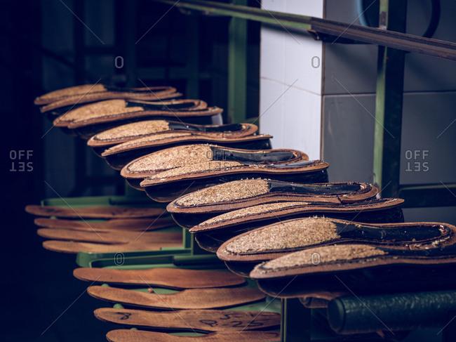 Set of handmade footwear and various soles lying on shelf in shoe making workshop
