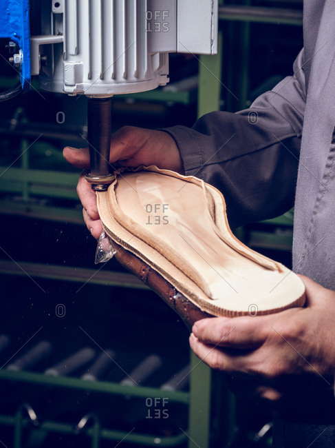 Anonymous man using professional machine to make good footwear while working on factory