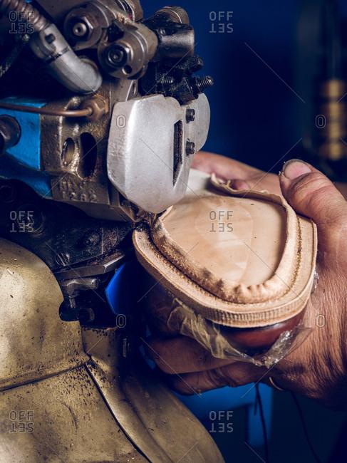 Crop craftsman making shoe on factory