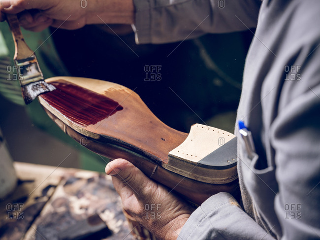 Crop shoemaker painting sole of footwear