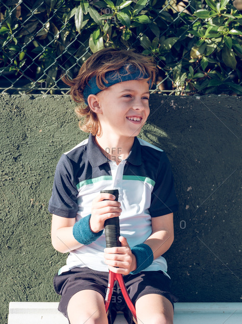Smiling little child with blue fillet and tennis racket on seat looking away in sunny day