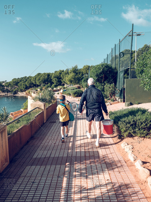 Old man with bucket and boy with tennis racket walking near water