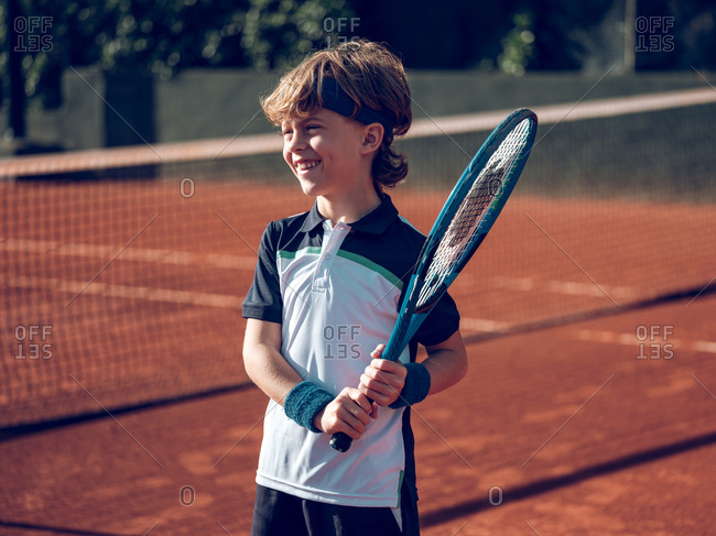 Smiling little child holding tennis racket near tennis net on court in sunny day