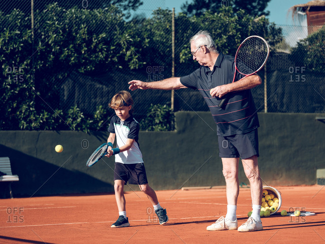 Aged male with tennis racket teaching little child to play tennis near pail with balls on court in sunny day