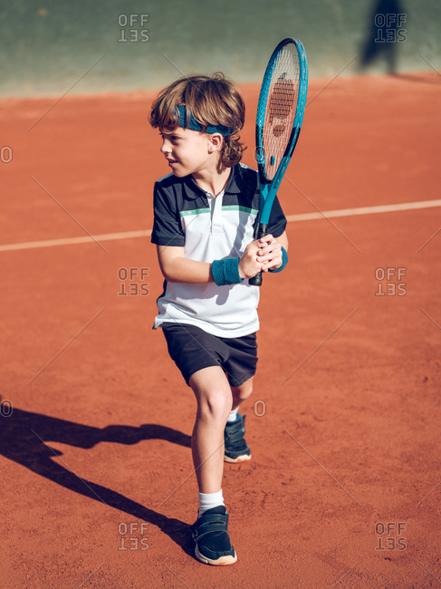 Little child in sportswear with tennis racket trying to hit suspended ball in air on court in sunny day