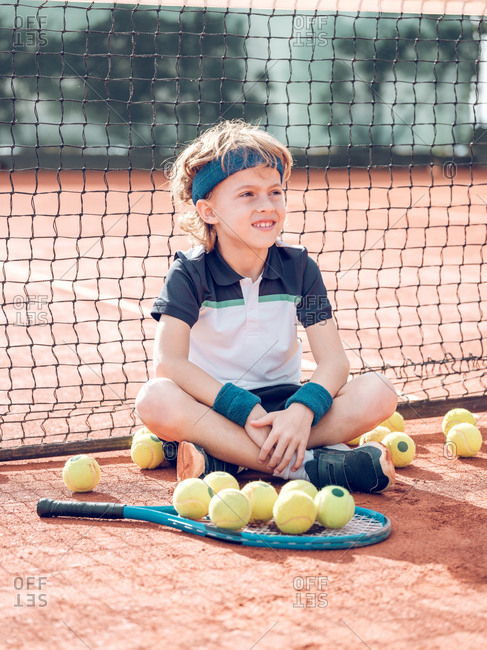 Little child with tennis racket and sitting near tennis net between scattering balls on court in sunny day
