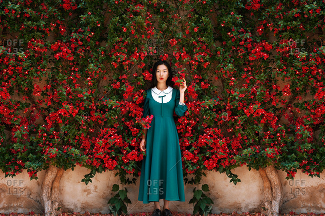 Attractive Asian lady in retro dress looking at camera while standing near wall with branches of amazing blooming plant