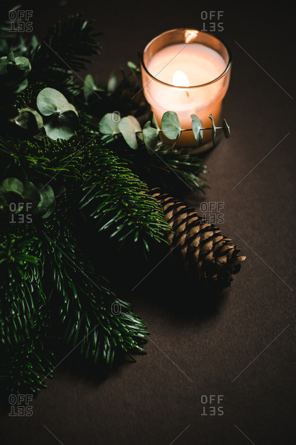 Small glass with flaming candle standing near green twigs and fresh cone of conifer tree on brown background