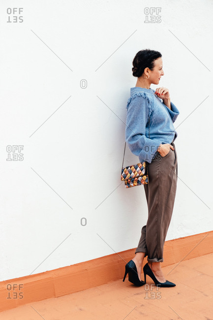 Side view of mature happy woman wearing trendy sweater with heels and standing with clutch bag outdoors