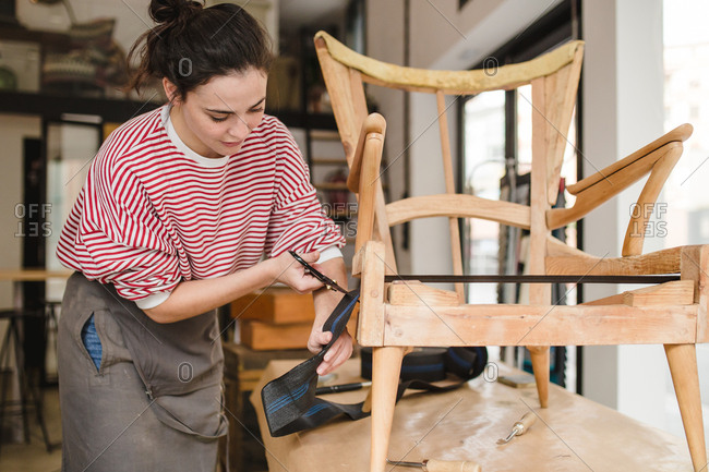 Young furniture restorer woman working and repairing chair
