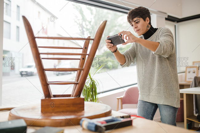 Young craftswoman taking a picture of an old wooden chair