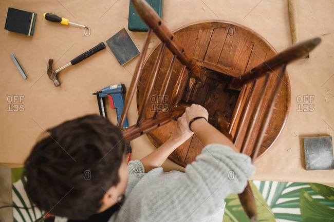 View from above of craftswoman repairing a wooden chair