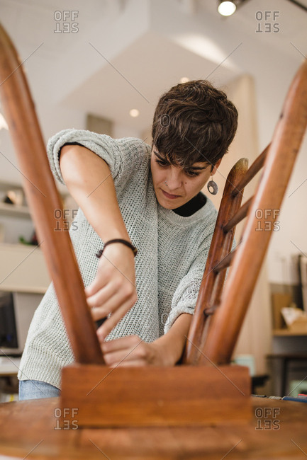 Front view of young craftswoman sanding and repairing a wooden chair