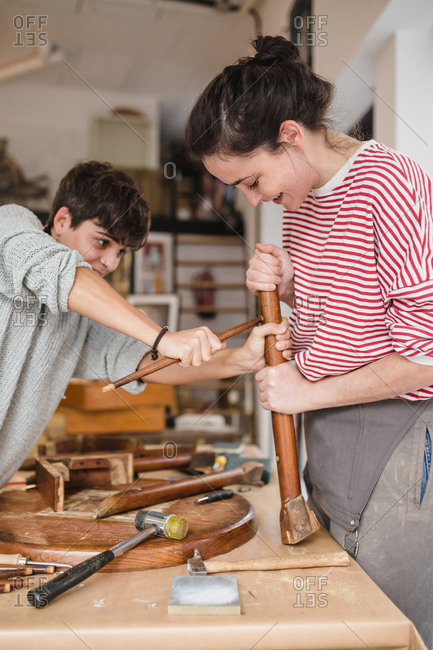 Side view of young craftswomen working and repairing an old wooden chair