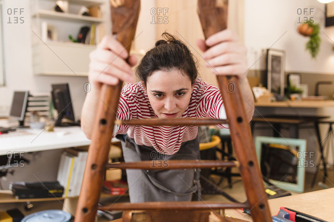 View through a chair of young craftswoman restoring