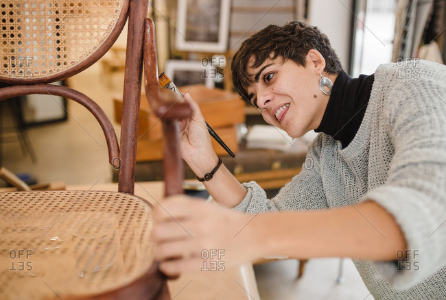 Front view of young furniture restorer varnishing an old wooden chair