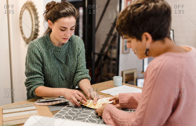 Two women interior designers discussing about blueprints