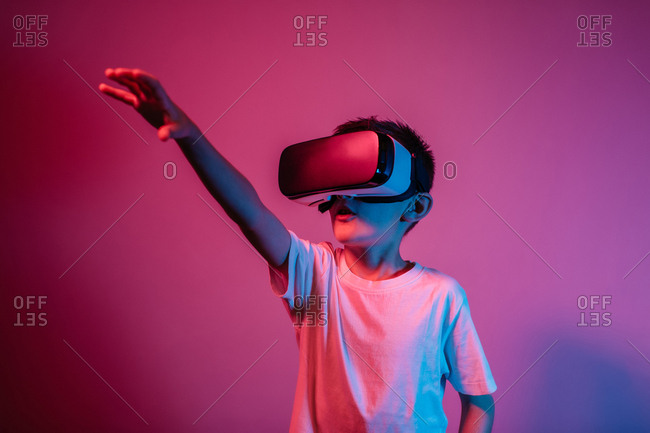 Boy wearing VR glasses against red and purple background. Portrait of child with virtual reality headset under neon lights.