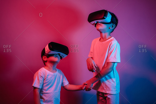 Kids holding hands and wearing VR glasses against red and purple background. Portrait of two children with virtual reality headsets under neon lights.