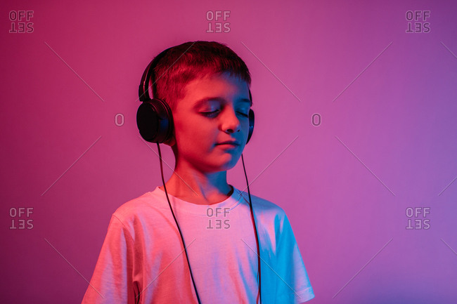Young boy with eyes closed listening to music in neon lights - studio shot. Portrait of child with headphones isolated over red and purple background.