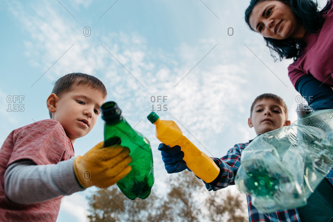 Low angle shot of woman and her sons holding plastic bottles against blue sky. Bottom view of female volunteer and her children showing empty plastic bottles into camera.