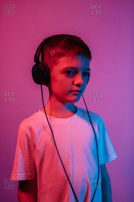 Young boy listening to music in neon lights - studio shot. Portrait of child with headphones isolated over red and purple background.