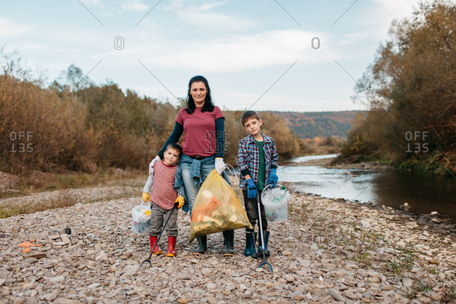 Front view of woman and her children cleaning plastic waste around river beach. Portrait of family volunteers holding plastic bags and buckets filled with rubbish.